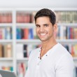 Smiling man holding a tablet in front of bookshelf — Stock Photo