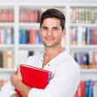 Male Student Holding Binder In Library — Stock Photo #27009899