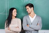 Studenter med armarna korsade tittar på varandra mot chalkbo — Stockfoto