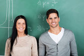 Two students standing in front of blackboard — Stock Photo