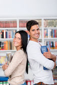 Students Holding Binders While Standing Back To Back In Library — Stock Photo