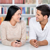 Cute couple looking at each other in library — Stock Photo
