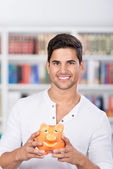 Male Student Holding Piggybank In Library — Stock Photo