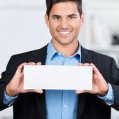 Businessman Holding Blank Placard In Office — Stock Photo