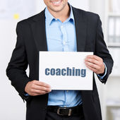 Businessman Holding Placard With Coaching Sign — Stock Photo