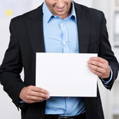 Businessman showing a blank white sheet — Stock Photo