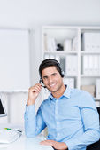 Customer Service Executive Communicating On Headset At Desk — Stock Photo