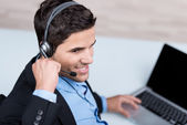Male Customer Service Executive Conversing On Headset At Desk — Stock Photo