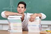 Serieuze student met stapels van schoolboeken — Stockfoto