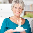 Senior Woman Holding Birthday Cake With Lit Candles At Home — Stock Photo
