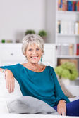 Senior Woman Sitting On Sofa At Home — Stock Photo