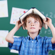 Young elementary schoolboy with a book over head — Stock Photo