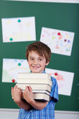 Young elementary schoolboy holding a pile of books — Stock Photo
