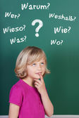 Schoolgirl with doubts in front of the blackboard — Stock Photo
