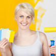 Happy Woman Holding Out Color Samples And Paint Roller — Stock Photo #27069993