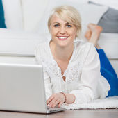 Relaxed woman with laptop lying on the floor — Stock Photo