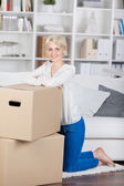 Woman leaning on cardbord boxes at home — Stock Photo