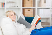 Smiling woman relaxing with a book — Stock Photo