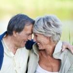 Sweet elderly couple in love sitting near the lake — Stock Photo