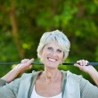 Happy older woman with a golf stick — Stock Photo