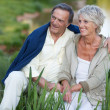 Happy elderly couple sitting on the lake — Stock Photo