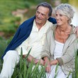 Happy elderly couple sitting on the lake — Stockfoto