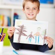 Stock Photo: Happy Little Boy Displaying Drawing At Table