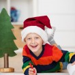 Boy with santa hat writing wish list — Stock Photo