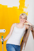 Smiling woman leaning on ladder — Fotografia Stock