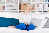 Mulher relaxada sentada com o laptop no sofá — Foto Stock