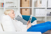 Young Woman With Tablet Sitting On Sofa — Foto de Stock