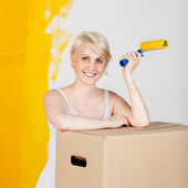 Woman With Cardboard Box And Paint Roller — Stock Photo