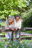 Old couple standing on a bridge inside a park — Stock Photo
