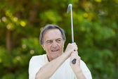 Elderly man with golf stick in action — Stock Photo