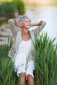Senior Woman With Hands Behind Head Relaxing By Lakeside — Stock Photo
