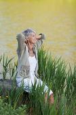 Senior woman sitting near a lake for fresh breathe — Stock Photo