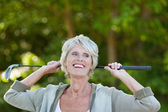 Senior frau gedrückt, dass golf club wegsehen — Stockfoto