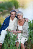Loving Senior Couple Sitting By Lakeside In Park — Stock Photo