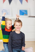Young Boy With Wild Brother Raising Arms — Stock Photo
