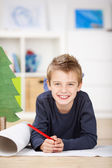 Happy Boy Drawing On Chart Paper While Lying On Floor — Stock Photo