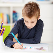 Boy Using Colored Pencil While Drawing On Paper At Table — Stock Photo