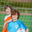 Two young players in front of soccer goal — Stock Photo #27099195