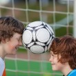Two friends balancing soccer ball between heads — Stock Photo #27099505