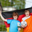 Stock Photo: Boys With Trophy And Soccer Ball Holding German Flag Against Net