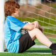 Sad looking boy leaning at goal — Stock Photo #27099707