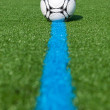 Ball lying on artificial turf — Stock Photo