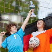 Two young soccer players celebrating with trophy — Stock Photo