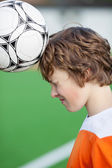 Teenage boy headering the ball at soccer — Stock Photo
