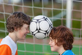 Two friends balancing soccer ball between heads — Stock Photo