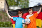 мальчики с трофей и футбол мяч холдинг немецкий флаг против net — Стоковое фото